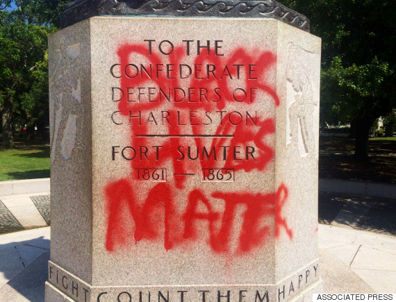 A statue memorializing the Confederacy is spray-painted with the message